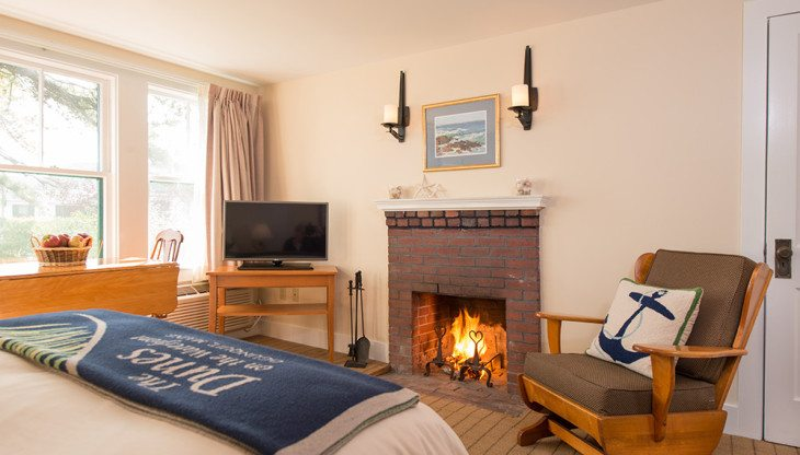 view of fireplace, television, and lounge chair from the bed
