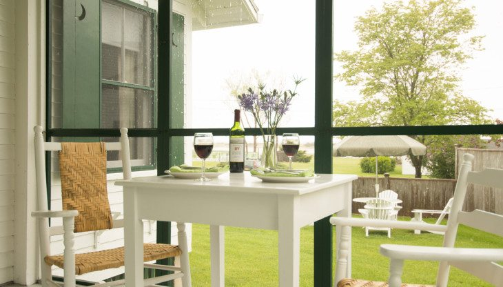 screened in porch with chairs and wine glasses on a table